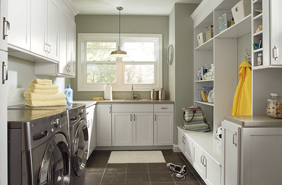 Green laundry room with white cabinets